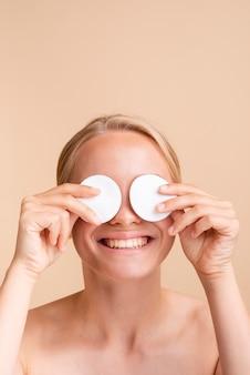 Close-up mujer cubriendo sus ojos con almohadillas de algodón