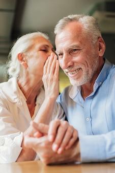 Close-up mujer diciendo a hombre un secreto