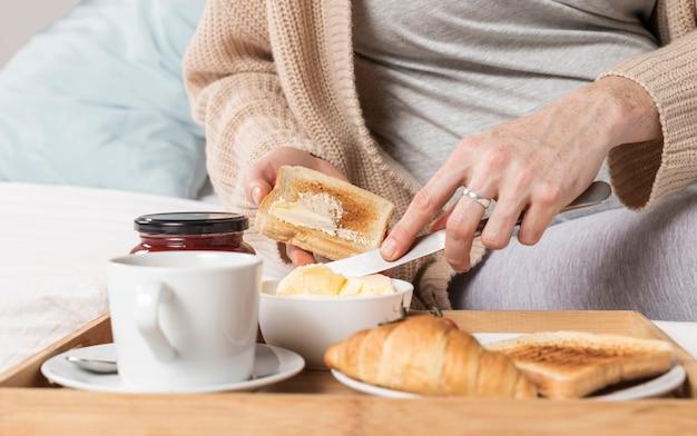 Close-up mujer embarazada comiendo brunch en la cama