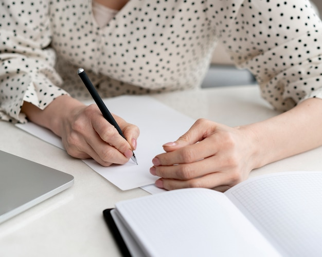 Close-up mujer escribiendo papeles