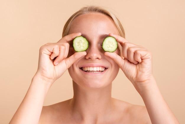 Close-up mujer feliz con rodajas de pepino