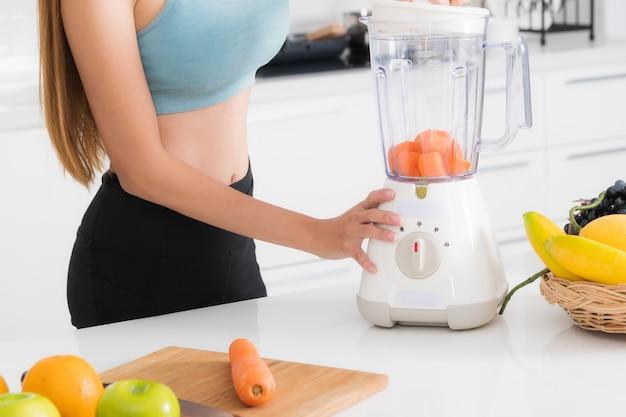 Close-up mujer haciendo jugos de frutas y verduras con licuadora.