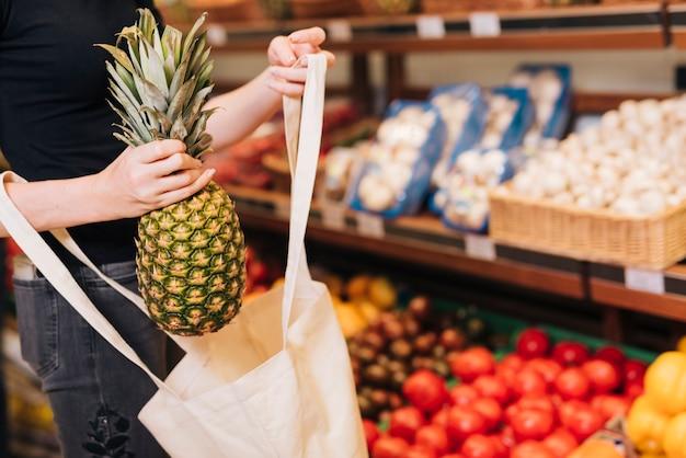 Close-up mujer poniendo una piña en una bolsa