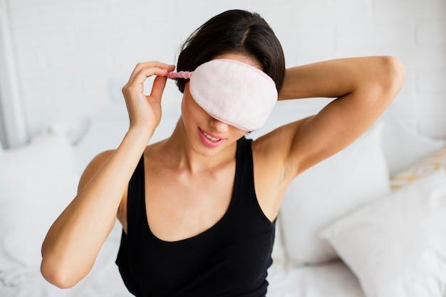 Close-up mujer poniéndose máscara para dormir