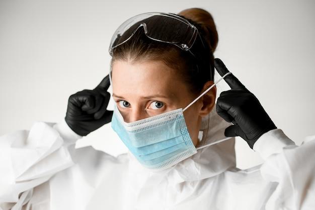 Close-up mujer en ropa protectora y guantes negros poniéndose una máscara en la cara