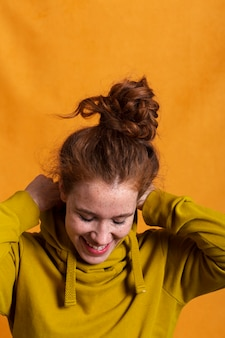 Close-up mujer sonriente arreglando su sudadera con capucha amarilla