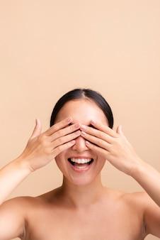 Close-up mujer sonriente cubriendo sus ojos