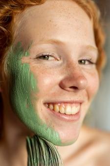 Close-up mujer sonriente pintando su rostro