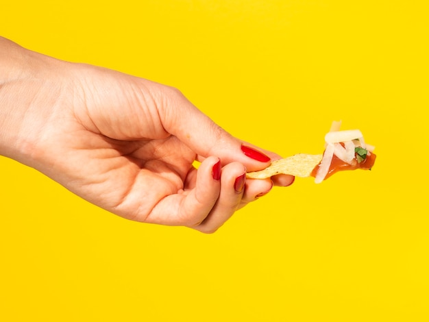 Close-up mujer sosteniendo chips de tortilla con fondo amarillo