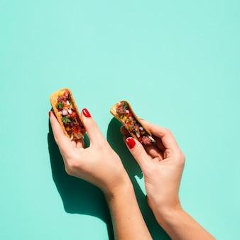 Close-up mujer sosteniendo pequeños tacos con espacio de copia