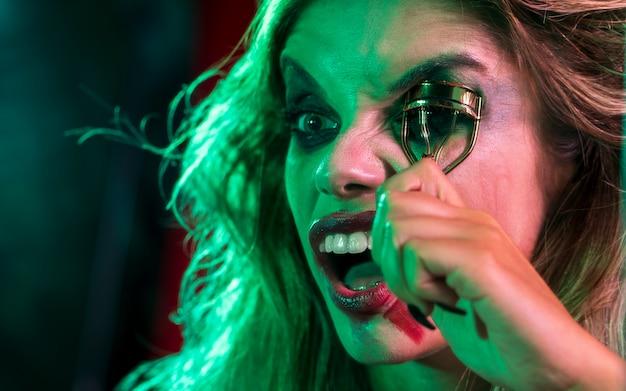 Close-up mujer vestida como bromista usando un rizador de pestañas