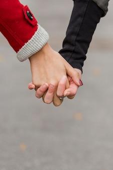 Close-up mujeres jóvenes manos tomados de la mano