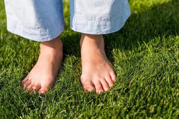 Close-up niña descalza de pie sobre el césped