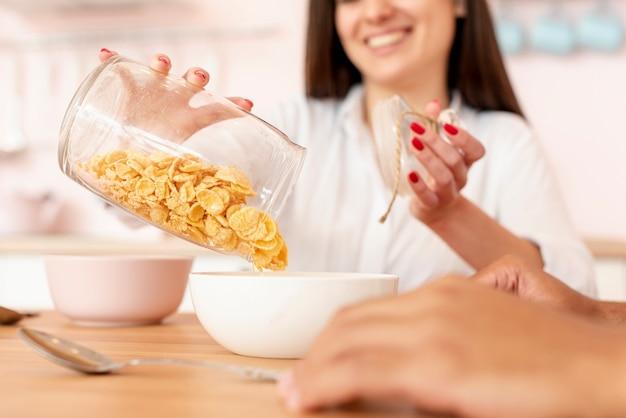 Close-up niña sonriente vertiendo cereales en un tazón