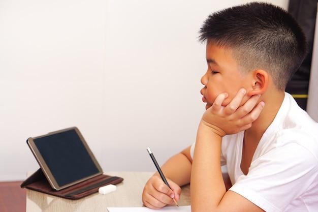 Close up un niño asiático con una camiseta blanca mirando la tableta digital encuentra la información (el niño está pensando) y está haciendo la tarea o escribiendo un cuaderno con un lápiz sobre la mesa.