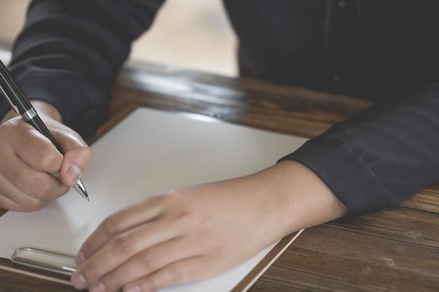 Close up of hand holding pen, es como un escritor de cartas