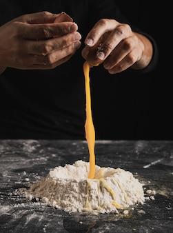 Close-up panadero manos separando los huevos en la composición de la masa