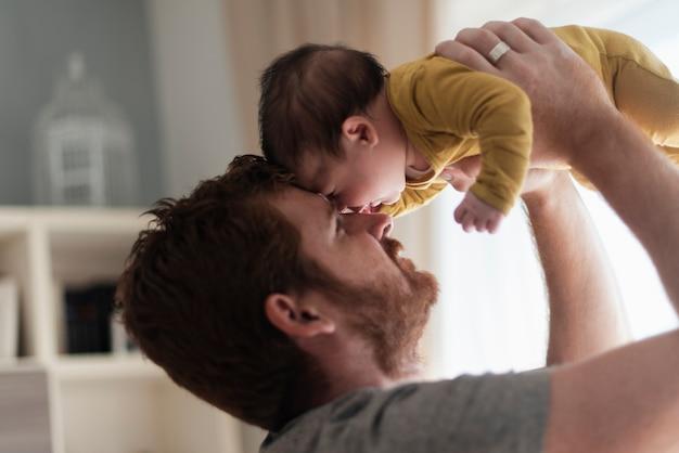 Close-up papá sosteniendo al bebé