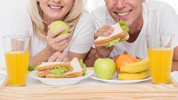 Close-up pareja feliz comiendo juntos