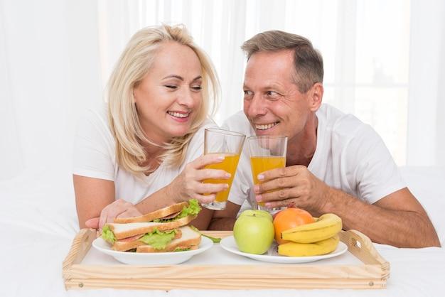 Close-up pareja feliz haciendo un brindis con jugo