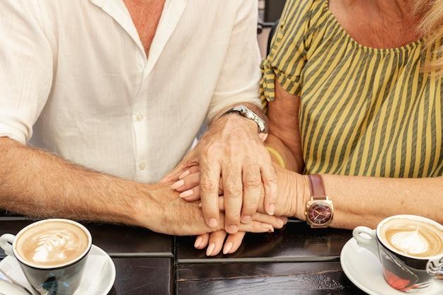 Close-up pareja tomados de la mano juntos