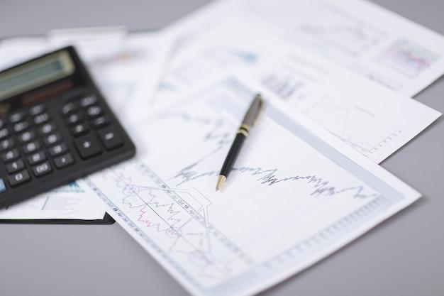 Close up.pen, gráfico financiero y calculadora en el escritorio.