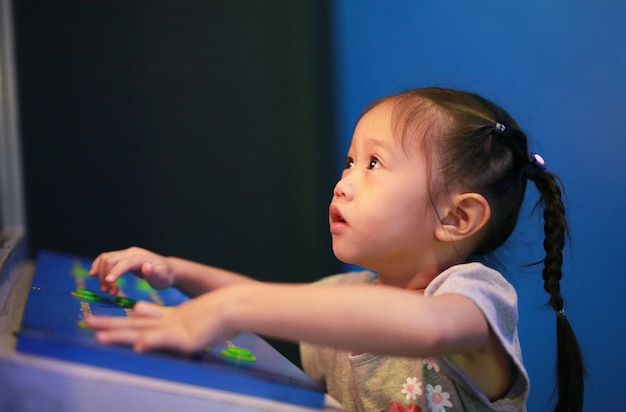 Close-up pequeña niña asiática niño jugando videojuegos arcade.
