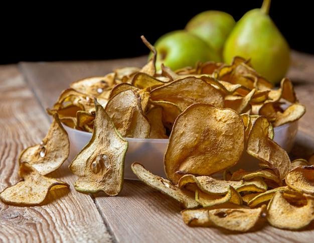 Close-up peras secas en placa y peras frescas en mesa de madera