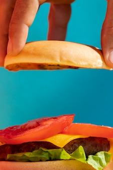 Close-up persona sosteniendo un bollo de hamburguesa con fondo azul.