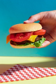 Close-up persona sosteniendo sabrosa hamburguesa con queso