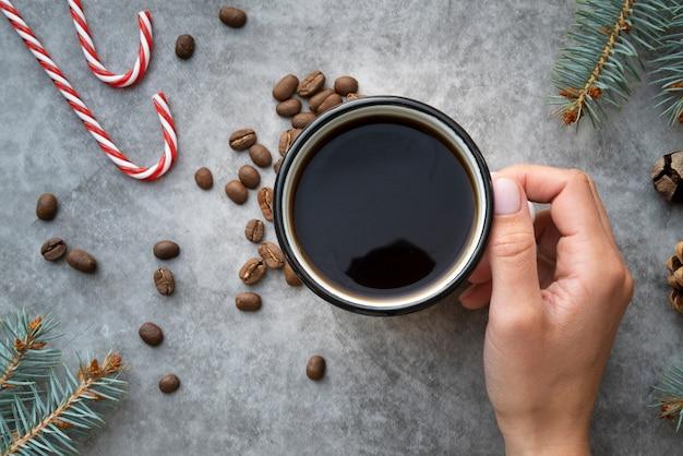 Close-up persona sosteniendo la taza de café con fondo de estuco
