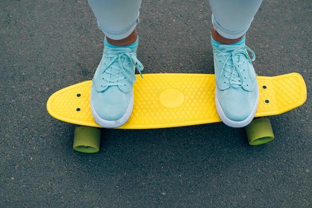 Close-up de piernas femeninas en jeans y zapatillas azules de pie sobre una patineta de plástico amarillo