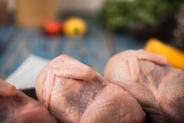 Close-up pollo crudo sobre tabla de madera con ingredientes