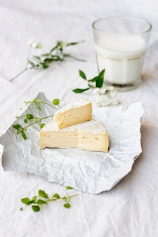 Close-up de queso brie con un vaso de leche