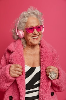 Close up retrato de abuela de moda arrugada feliz vistiendo abrigo y medias rosa