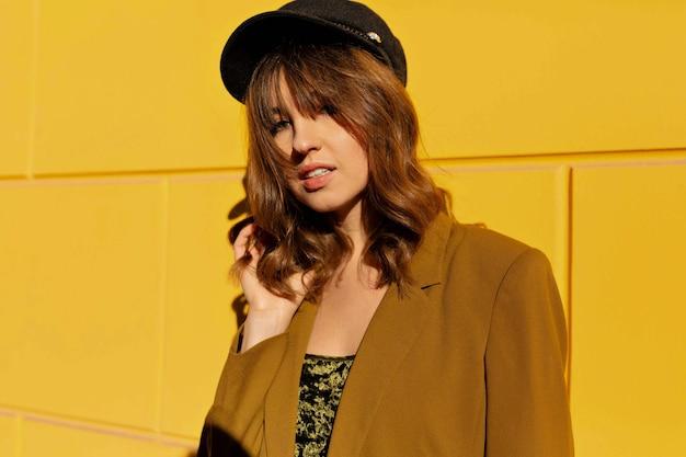 Close up retrato de adorable mujer encantadora con gorra negra y chaqueta mostaza posando en la luz del sol sobre la pared amarilla