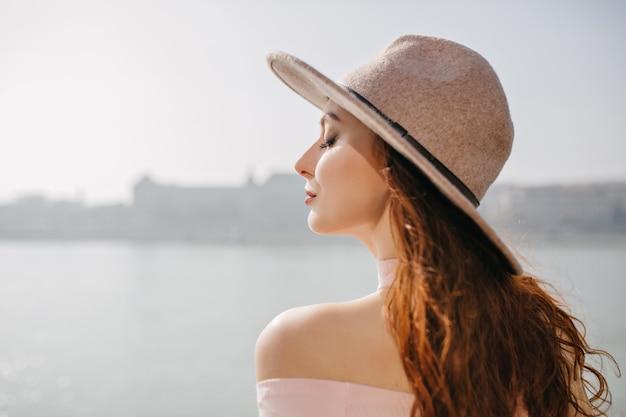 Close-up retrato al aire libre de dichosa mujer jengibre disfrutando de la brisa del mar