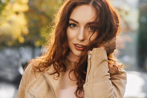 Close-up retrato al aire libre de hermosa mujer jengibre con ojos grandes lleva chaqueta beige