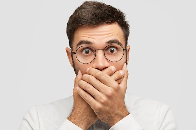 Close up retrato de apuesto joven cubre la boca con ambas palmas, trata de ser mudo, deja de gritar