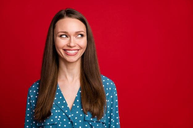 Close-up retrato de atractiva chica alegre alegre mirando a un lado copia espacio aislado sobre fondo de color rojo brillante