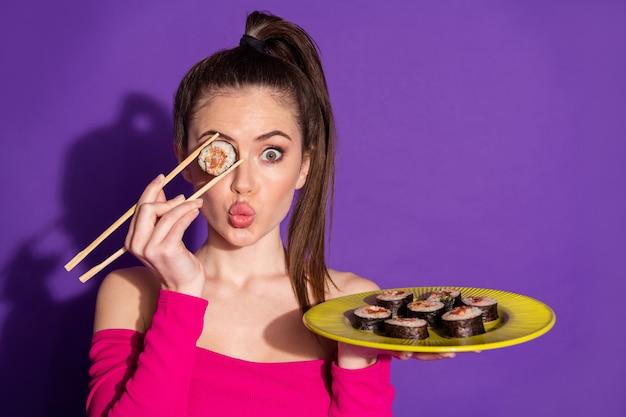 Close-up retrato de atractiva chica alegre funky comiendo roll pout labios cerrando el ojo aislado de fondo de color violeta brillante