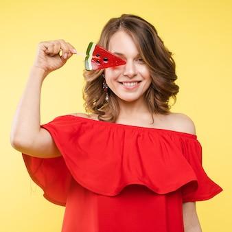 Close up retrato de atractiva chica encantadora en vestido ligero entregando lolipop aislado sobre fondo amarillo