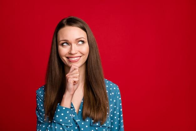 Close-up retrato de atractiva chica de pelo castaño alegre inteligente pensando espacio de copia aislado sobre fondo de color rojo brillante