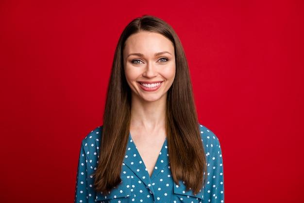 Close-up retrato de atractivo contenido alegre chica usar blusa punteada aislada sobre fondo de color rojo brillante