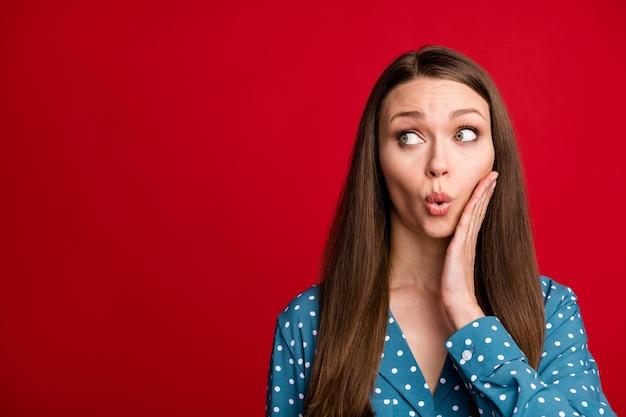 Close-up retrato de bastante sorprendida chica de cabello castaño mirando a un lado puchero labios copia espacio aislado sobre fondo de color rojo brillante