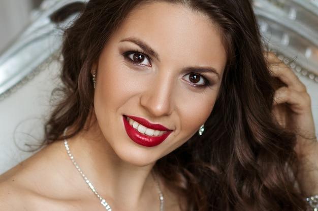 Close-up retrato de una bella mujer con maquillaje y labios rojos, cabello hermoso