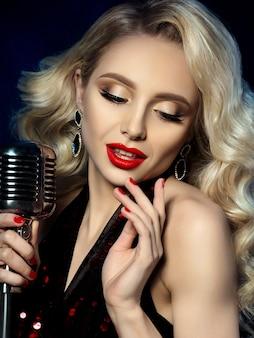 Close up retrato de cantante bastante rubia sosteniendo micrófono de estilo retro