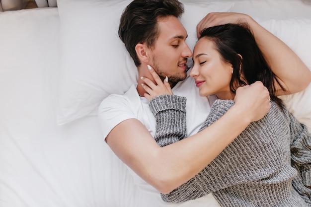 Close-up retrato de chico guapo abrazando suavemente a la mujer de pelo negro que duerme al lado