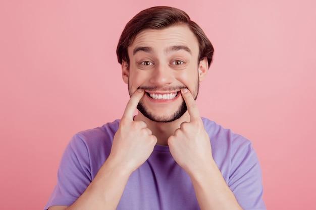 Close up retrato de chico positivo feliz positivo indicar dedos dentudos sonrisa cuidado bucal aislado sobre fondo de color rosa