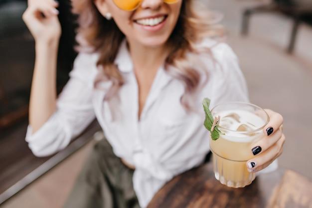 Close-up retrato de dama sonriente en camisa blanca con mano sostiene un vaso de café helado en primer plano